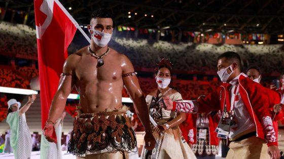 Pita Tufatofua con abdomen descubierto, embarrado con aceite de coco, sosteniendo la bandera en los Juegos Olímpicos de Tokio 2020 Foto: AFP